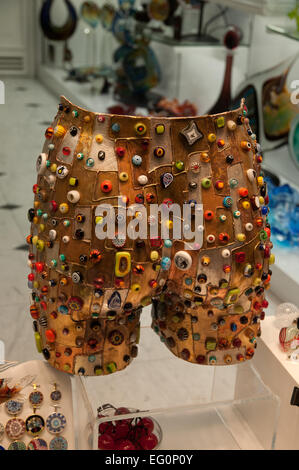 Murano glass artwork on sale in shop on Calle Lungha Venice Italy depicts pair of shorts with multiple ornaments - Stock Image