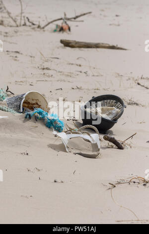 Plastic rubbish washed up on a beach and part buried in the sand an example of the many pieces of garbage in the oceans around the world - Stock Image
