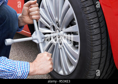 Close Up Of Man With Tyre Iron Changing Car Wheel - Stock Image