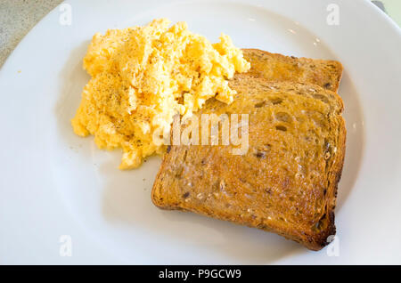 Scrambled eggs on two slices of buttered toasted bread ready to eat - Stock Image