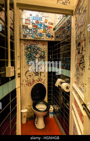 A toilet covered in grafitti inside a London pub - Stock Image