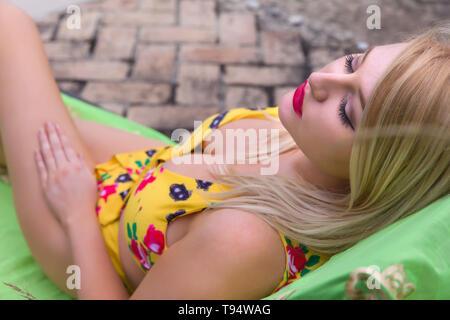 Sexy blonde woman in yellow bikini posing at the poolside - Stock Image