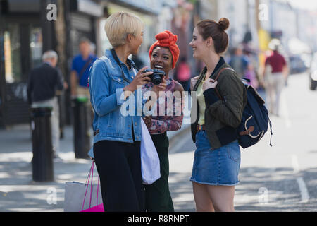 Young women friends with camera on urban sidewalk - Stock Image