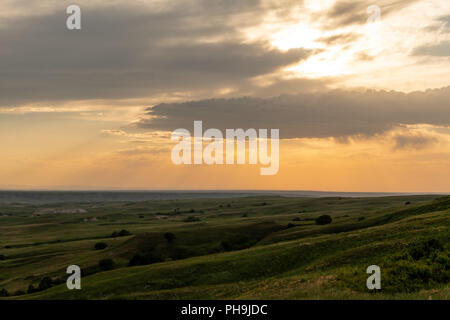 Orange Sky and Clouds Over Rolling Fields in Badlands - Stock Image