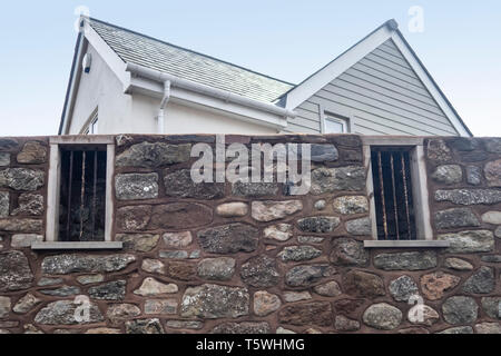 Old barred windows of Sidmouth Jail left in a wall as part of a new housing development. Town jail bars. - Stock Image