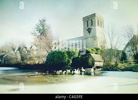 Church in Haddenham with frozen pond - Stock Image