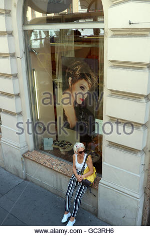 A fashionable mature woman in summer clothing sits on a window ledge of a fashion store, in Vienna, Austria. - Stock Image