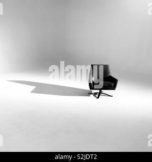 A chair in a white room. - Stock Image