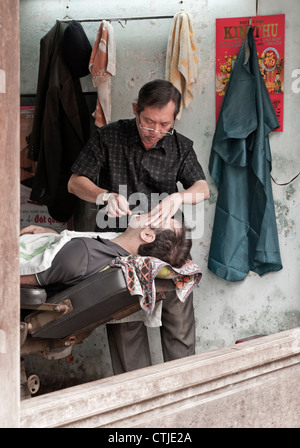 Traditional male barber hairdresser shaving customer in Hoi An, Viet Nam - Stock Image