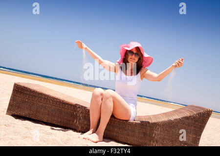 Young woman enjoying on a lounger on the beach - Stock Image