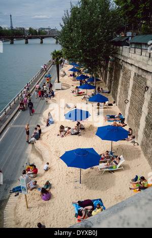 View of the artificial beaches set up by the Paris government during the summer period along the banks of the Seine river. - Stock Image