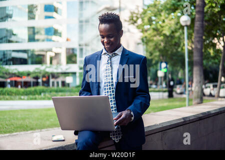African American businessman holding laptop notebook wearing blue suit - Stock Image
