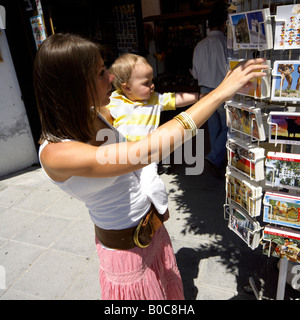 Mother and toddler buying postcards at Mijas Pueblo, Costa del Sol, Andalucia, Spain - Stock Image