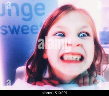 Young Child pulling a scary face. - Stock Image
