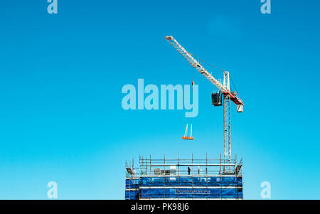 Gosford, New South Wales, Australia - August 29. 2018: Construction and building progress update 121.  A working tower crane on new home units buildin - Stock Image