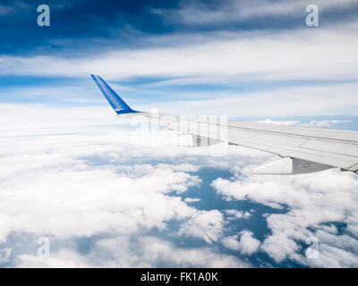 Airplane wing above the clouds with a blue sky - Stock Image