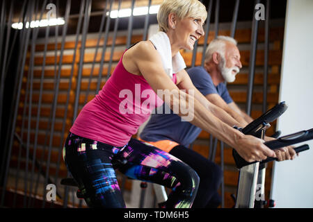 Happy fit mature woman and man cycling on exercise bikes to stay healthy - Stock Image