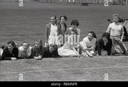 1950s, historical, secondary school children sitting together beside a grass running track watching  the action unfold in their school sports day, Englabd, UK. - Stock Image