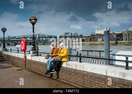 Tourists texting on their mobile phones and sitting on a wall on the South Bank in London. - Stock Image