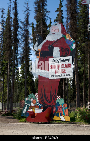 Statue of Father Christmas / Santa Claus standing besides his 'home'  in North Pole, Alaska. - Stock Image