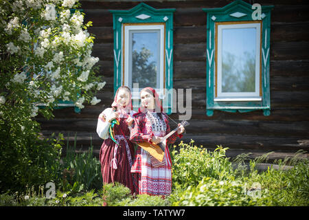 Two young women in traditional russian clothes stand in front of a wooden house one of theme play balalaika - wide angle - Stock Image