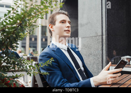 Young businessman holding mobile phone in hand and looking aside. Side view. - Stock Image