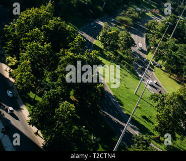 High angle aerial perspective of seemingly miniature cars on highway in between a park - deliberate dutch angle. - Stock Image