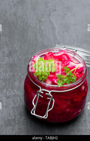 Salad  with cabbage and beetroot in glass jar on black stone background - Stock Image