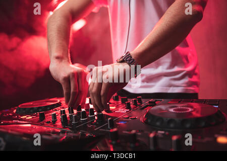 Dj mixing at party festival with red light and smoke in background - Summer nightlife view of disco club inside. Focus on hands - Stock Image