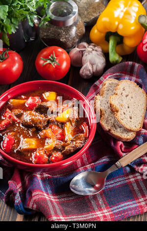 Traditional Hungarian beef goulash with red and yellow pepper - Stock Image