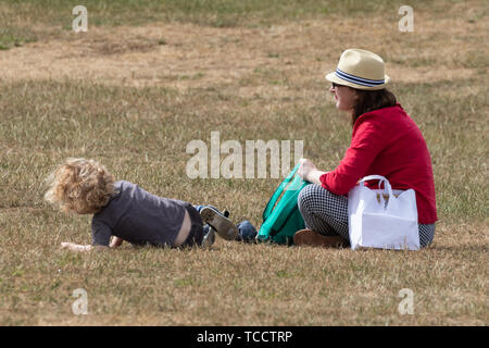 A mother and son sat on the grass in the park - Stock Image