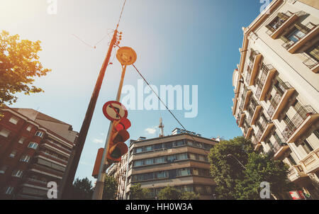 Wide angle view of red traffic light and electric pole at the crossroad surrounded by beige and red residential - Stock Image