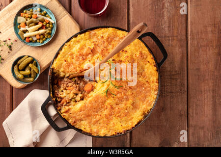 Shepherd's pie with pickles, herbs, and red wine, top shot on a dark rustic wooden background - Stock Image