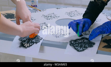 Women decorators, designers painting wooden circle decoration - Stock Image