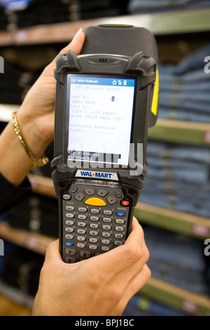 A sales associate uses a Telxon handheld scanner to read EPC/RFID labels at a Walmart Supercenter in Rogers, Ark. - Stock Image