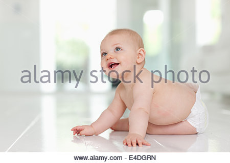 Smiling baby with balloons on floor - Stock Image