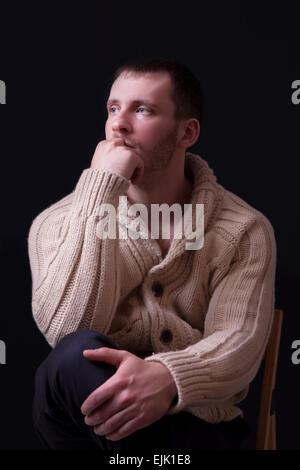 Portrait of handsome and young man in sweater on black background. - Stock Image