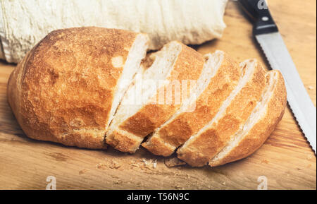Ciabatta bread loaf slices on wooden board with knife. Fresh crusty white whreat bread italian cuisine - Stock Image
