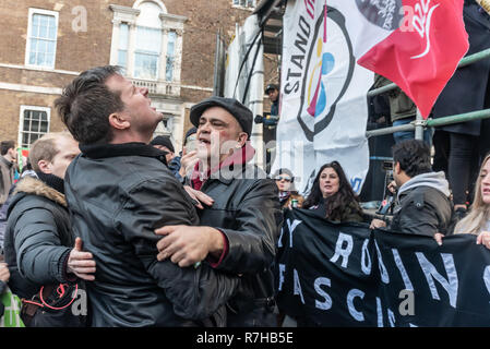London, UK. 9th Dec, 2018. People argue with a heckler at the rally by united anti-fascists in opposition to Tommy Robinson's fascist pro-Brexit march. The protest by both remain and leave supporting anti-fascists gathered at the BBC and marched to a rally at Downing St. Police had issued conditions on both events designed to keep the two groups well apart. Credit: Peter Marshall/Alamy Live News - Stock Image