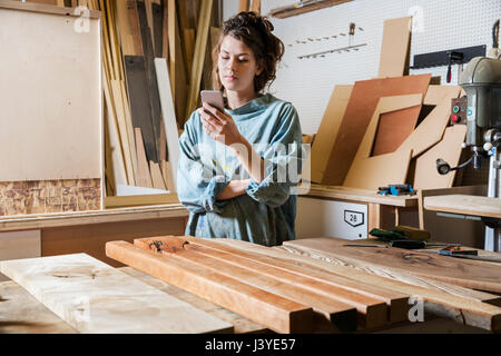 Young woman texting in a wood workshop - Stock Image