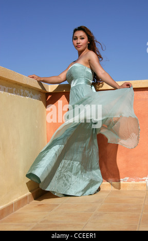 Indonesian Girl in a Turquoise Dress Standing by a Yellow and Orange Wall, Fuerteventura, Canary Islands, Spain. - Stock Image