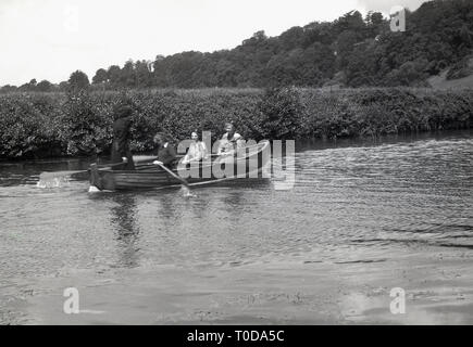 1930s, girl guides in a rowing boat going down a river, England, UK. - Stock Image