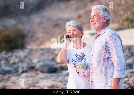 Happy cheerful aged old caucasian couple enjoy and have fun together in outdoor - together forever life concept for beautiful man and woman retired - Stock Image