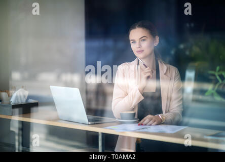 Woman working on laptop at coffee shop. Window Reflexions. Shot of a young woman using a laptop in a cafe - Stock Image