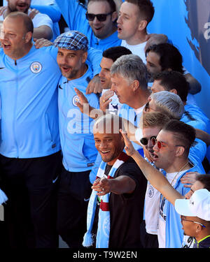 Manchester City manager Pep Guardiola (flat cap top) and Vincent Kompany (centre) on stage during the trophy parade in Manchester. - Stock Image