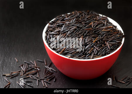 Black wild rice in a red bowl on a black background - Stock Image