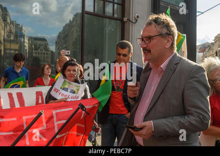 London, UK. 13th August 2018.  A speaker brings solidarity from the TUC to the Brazilians protesting outside the Brazilian embassy calling for the release of Luiz Inacio Lula da Silva, a former trade union leader who was President of Brazil from 2003-11 to enable him to stand for election again in October. Credit: Peter Marshall/Alamy Live News - Stock Image