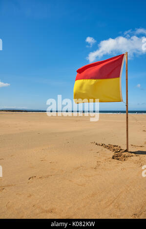 Red and yellow warning flag against a blue sky advising swimmers on the beach at Ballybunion, County Kerry Ireland - Stock Image