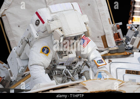 Expedition 59 NASA astronauts Anne McClain works upgrading the power supply during a spacewalk outside the International Space Station March 22, 2019 in Earth Orbit. Astronauts McClain and Hague spent six-hours and 39-minutes outside the space station to upgrade the orbital complex's power storage capacity. - Stock Image