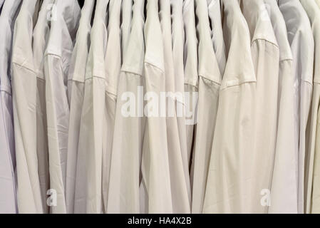 Rows of mens formal business shirts hanging from a hanger - Stock Image